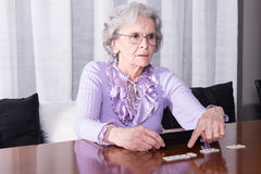 Active female senior playimg at the table Royalty Free Stock Photography