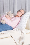Active female senior relaxing on couch Royalty Free Stock Photo