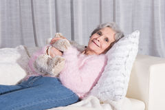 Active female senior relaxing on couch Stock Photo