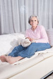 Active female senior relaxing on couch Royalty Free Stock Photography