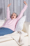 Active female senior stretching on couch Stock Image