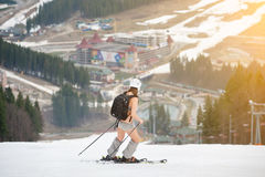 Active female skier skiing on the snowy slope of the mountain, wearing ski equipment, backpack, helmet Royalty Free Stock Image
