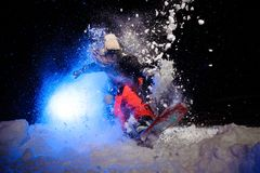 Active female snowboarder dressed in a orange sportswear jumping on the mountain slope. In the night under the blue light royalty free stock image