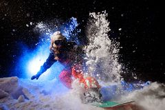 Active female snowboarder dressed in a orange sportswear riding on the mountain slope. In the night under the blue light royalty free stock photos