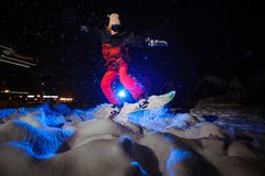 Active female snowboarder dressed in a red sportswear jumping on the mountain slope. In the night under the blue light stock photo