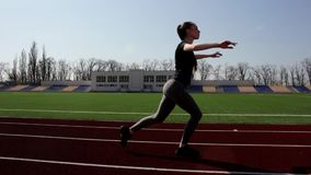 Active fit attractive young girl walking doing squats warming up stretching muscles outdoor working out at big stadium stock footage