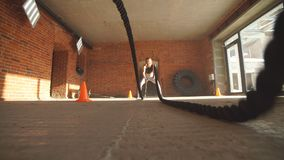 Active fit female athlet is doing battle rope. stock footage