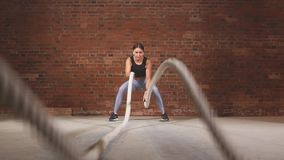 Active fit female athlet is doing battle rope. Slow motion stock footage