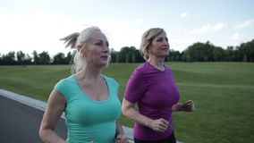 Active fit senior female athletes running outdoors stock footage