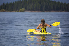 Active, Fit woman kayaking on a beautiful Mountain lake Royalty Free Stock Images