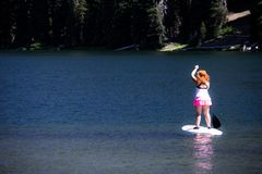Active fit woman on a Stand up paddle board boating on Todd Lake in the Cascade Lakes area royalty free stock photography