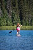 Active fit woman on a Stand up paddleboard boating on Todd Lake Oregon. Active fit woman on a Stand up paddleboard boating on Todd Lake in the Cascade Lakes area stock photo