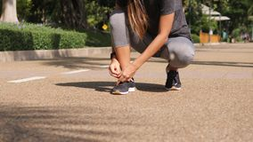 Active Fit Young Mixed Race Runner Girl Tying Shoe Laces in Park. 4K. Bangkok, Thailand. Active Fit Young Mixed Race Runner Girl Tying Shoe Laces in Park. 4K stock video footage