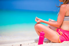 Active fit young woman in yoga position at her sportswear during beach vacation Stock Image