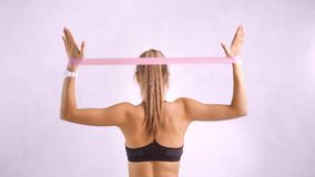Active fitness female showing exercise for back muscle using rubber band rear view isolated