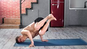 Active fitness male practicing yoga exercise on mat at home kitchen full shot. Athletic man with perfect muscular body making workout pilates training lifting stock video footage