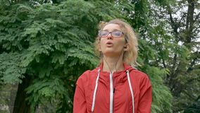 Active fitness woman in red clothes and eyeglasses is stretching outdoor in the park during spring or summer rainy. Morning. Healthy lifestyle concept, HD stock video footage