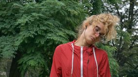 Active fitness woman in red clothes and eyeglasses is stretching outdoor in the park during spring or summer rainy. Morning. Healthy lifestyle concept, HD stock footage