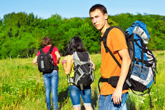 Active friends. Active young friends with backpacks hiking Royalty Free Stock Photography