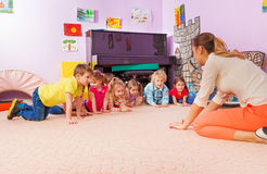 Active game kids and teacher stand on all fours Stock Image