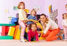 Active game in kindergarten kids go though hoops Stock Image