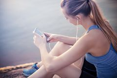The girl in a t-shirt sitting near the water with a smartphone and headphones after jogging. Royalty Free Stock Photos