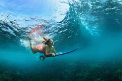 Active girl in bikini in dive action on surf board. Active girl in bikini in action. Surfer woman with surf board dive underwater under breaking big wave royalty free stock photography