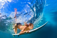 Active girl in bikini in dive action on surf board. Active girl in bikini in action. Surfer woman with surf board dive underwater under breaking big wave royalty free stock photo