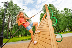 Active girl climbs on wooden construction Royalty Free Stock Images