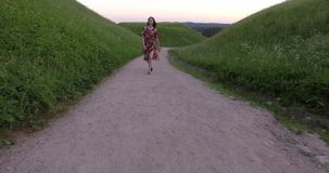 Active girl in colorful dress walking on gravel way. Handheld shot. Active girl in colorful dress walking on gravel way. Handheld follow shot stock video