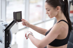 Active girl controlling her weight and pulse in gym Royalty Free Stock Images