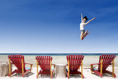 Active girl jump over beach chairs royalty free stock images