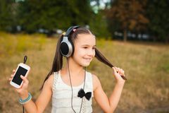 Active girl with long hair listening song. Active girl with long hair having nice rest outdoor, little girl with black and silver headphone listening song on Stock Images