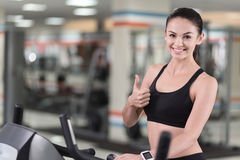 Active girl making an approving gesture with her thumb up. Love for sport. Active young smiling woman making an approving gesture holding her thumb up while Royalty Free Stock Photography