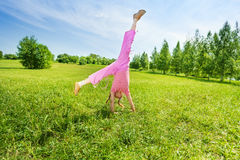 Active girl making flip on grass outside Royalty Free Stock Image