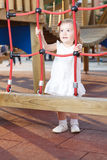 Active girl in playground. Holding on to ropes Royalty Free Stock Photo