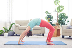 Active girl in sportswear doing backbend sequence pose Stock Image
