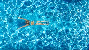 Active girl in swimming pool aerial drone view from above, young woman swims in blue water, tropical vacation, holiday on resort. Concept stock images