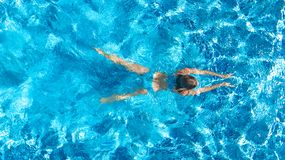 Active girl in swimming pool aerial drone view from above, young woman swims in blue water, tropical vacation, holiday on resort. Concept royalty free stock photography