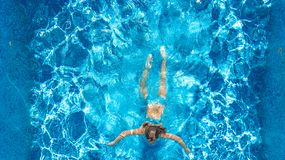 Active girl in swimming pool aerial drone view from above, young woman swims in blue water, tropical vacation, holiday on resort. Concept royalty free stock photos