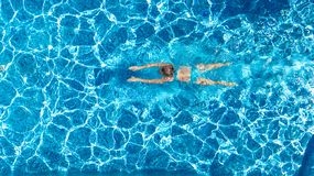 Active girl in swimming pool aerial drone view from above, young woman swims in blue water, tropical vacation, holiday on resort royalty free stock images