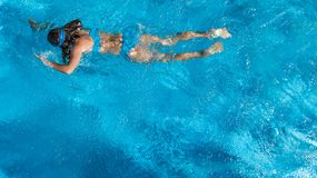 Active girl in swimming pool aerial drone view from above, young woman swims in blue water, tropical vacation, holiday on resort stock photos