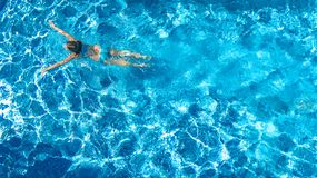 Active girl in swimming pool aerial drone view from above, young woman swims in blue water, tropical vacation, holiday on resort. Concept royalty free stock image