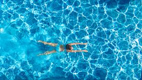 Active girl in swimming pool aerial drone view from above, young woman swims in blue water, tropical vacation, holiday on resort. Concept royalty free stock photo