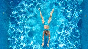 Active girl in swimming pool aerial drone view from above, young woman swims in blue water, tropical vacation, holiday on resort. Concept stock image