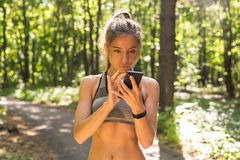Active girl using fitness tracker smart watch jogging on summer nature outdoors looking at health data during sports royalty free stock photo