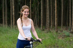 Active girl woman in forest with mountain bike Stock Image