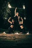 Active girls and boys carries out tricks for fire show at night Royalty Free Stock Images