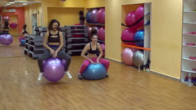 Active girls jumping on gymnastic balls in the gym, slow motion. stock footage