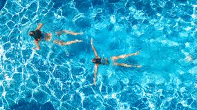 Active girls in swimming pool water aerial drone view from above, children swim, kids have fun on tropical family vacation. Holiday resort concept royalty free stock photography
